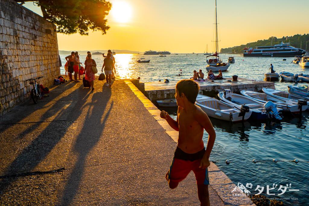 フヴァル島の夕日を背に走る少年